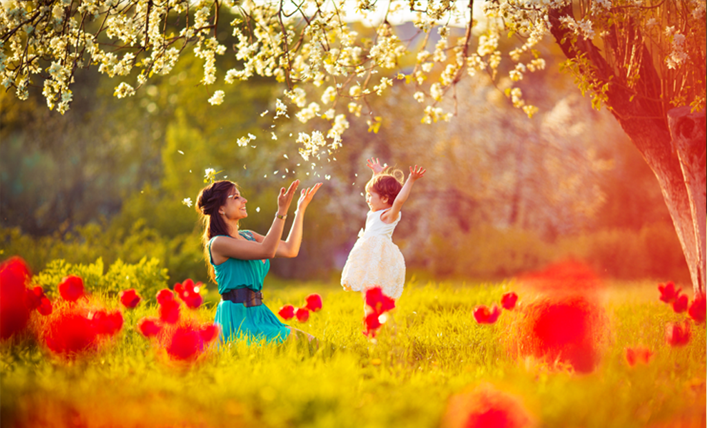 Birch Landing Apartments - Woman celebrating with young girl under a tree in a blooming field